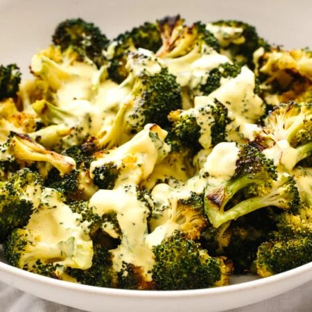 A bowl of roasted broccoli topped with hollandaise sauce.