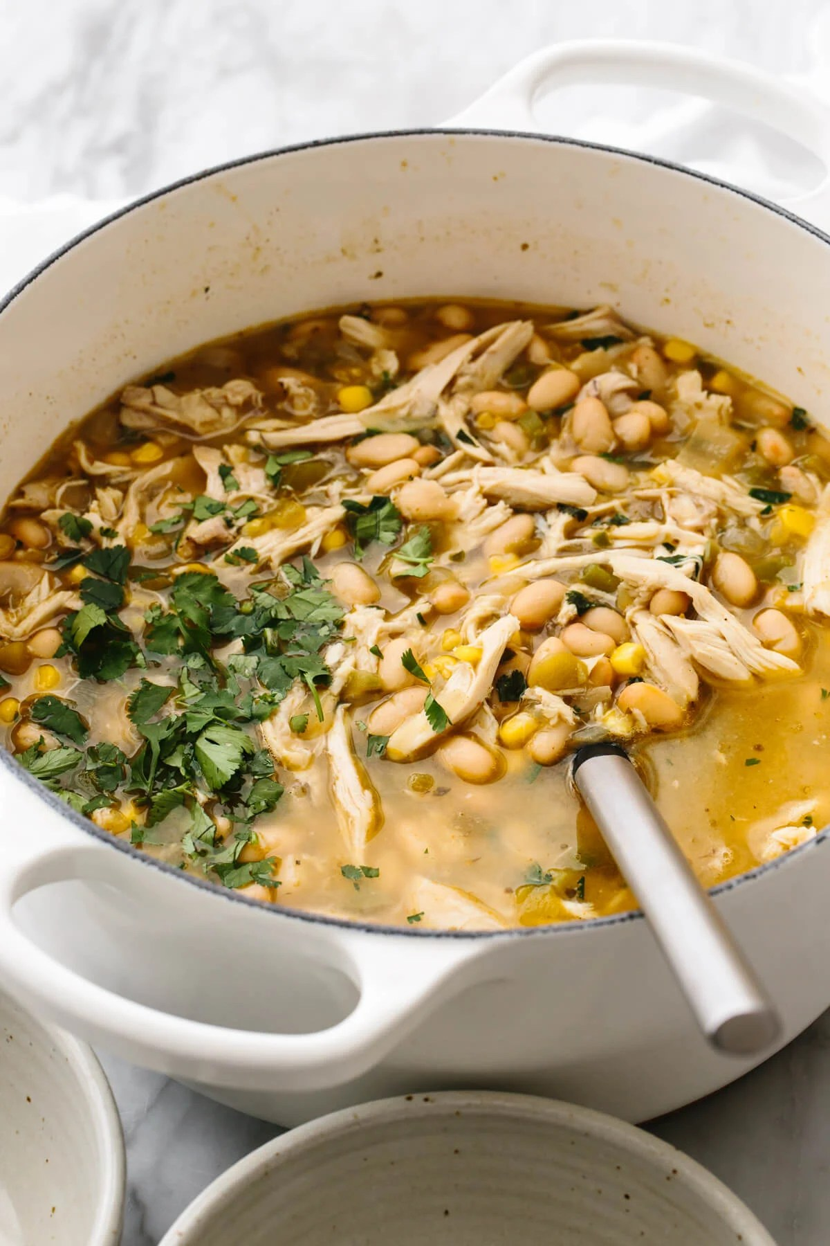 A big white pot of white chicken chili on a table.