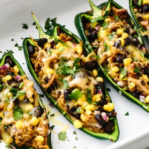 A baking dish of carnitas stuffed poblano peppers lined up