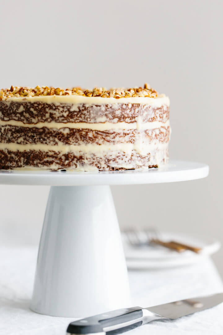 Triple layer gluten-free carrot cake on a cake stand.