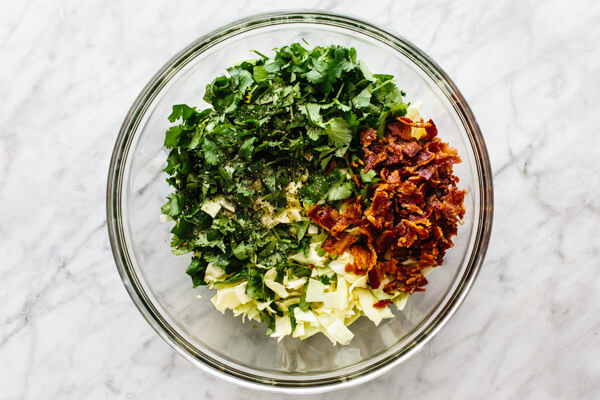 Mixing cilantro lime bacon coleslaw in a bowl.