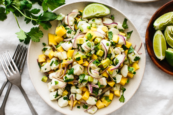 Mango halibut ceviche on a plate next to forks and cilantro.