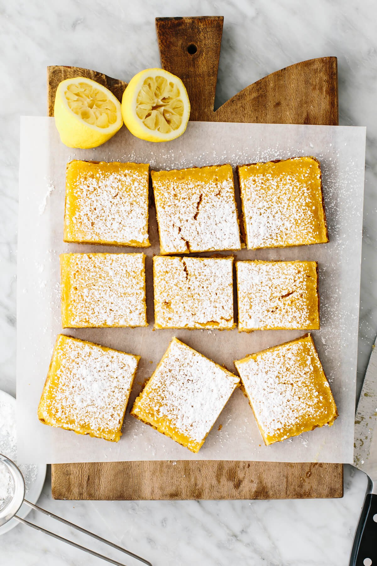 A board with lemon bars on top and lemons.