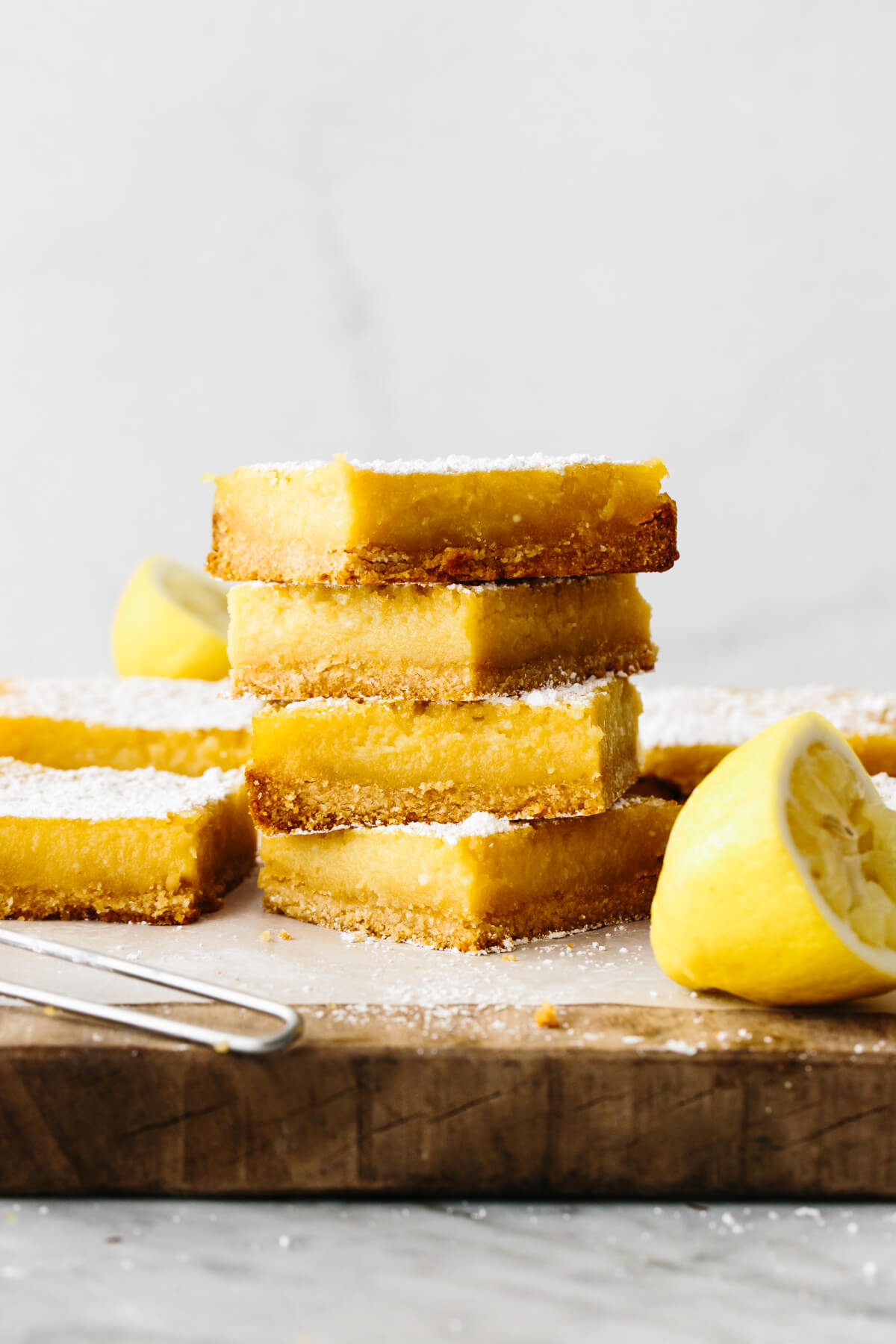 A pile of lemon bars on a wooden board.