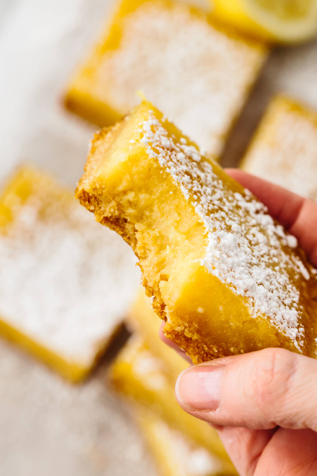A bite out of a lemon bar.