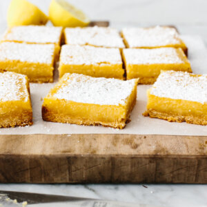 Sliced lemon bars on a wooden board.