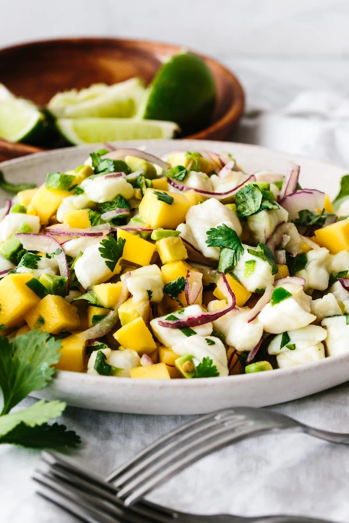 A plate of mango halibut ceviche next to forks.