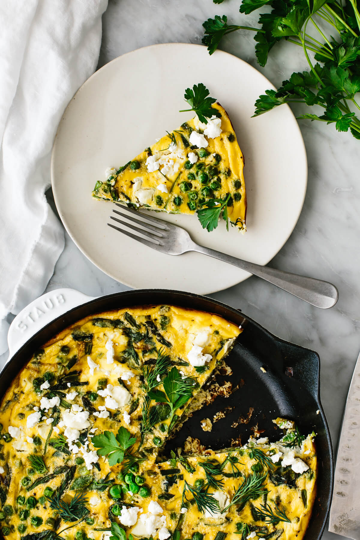 A skillet of spring vegetable frittata next to a plate with a fork.