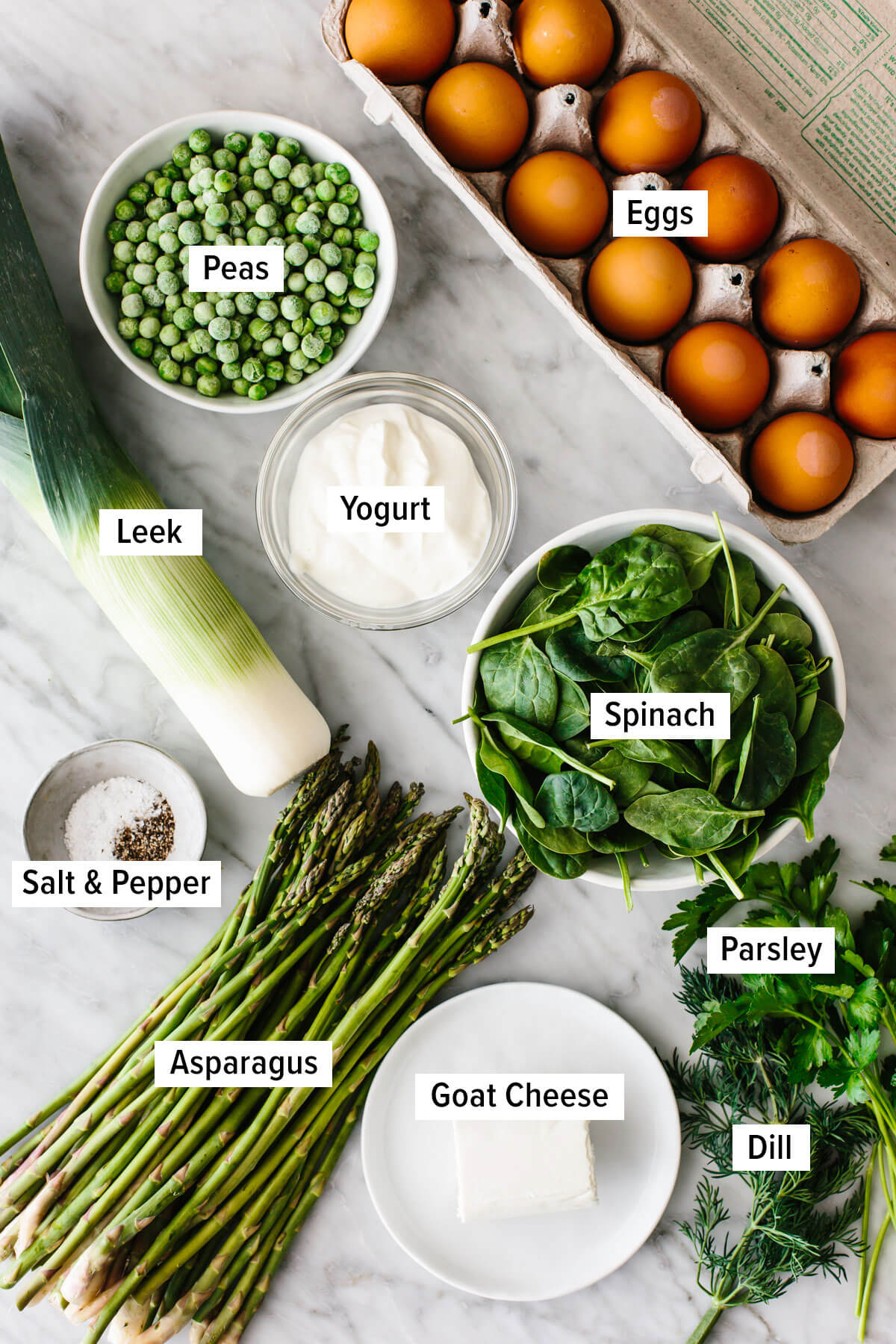Ingredients for a spring vegetable frittata on a table.