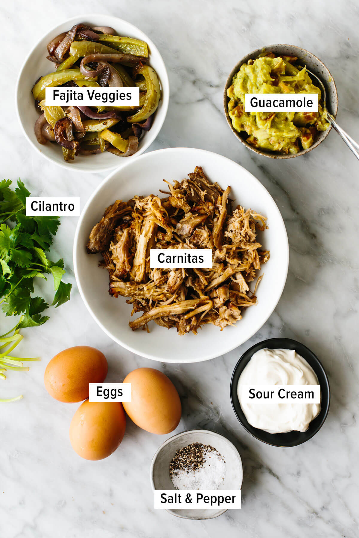 Ingredients for a carnitas omelette on a table.