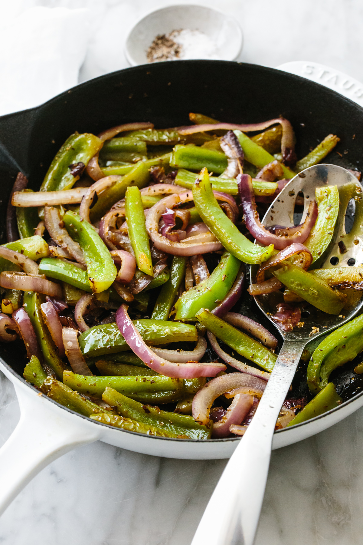 Fajita veggies in a skillet with a slotted spoon.