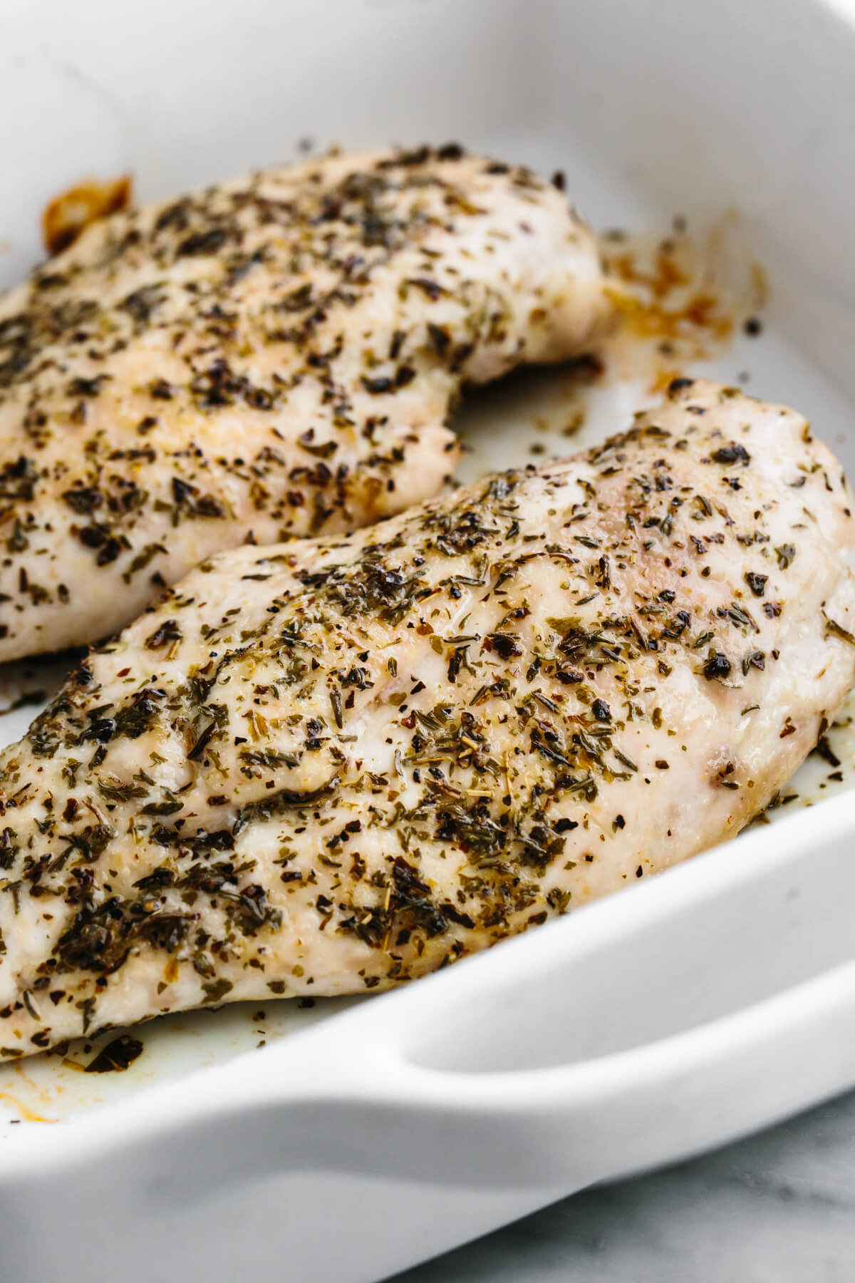 A baking dish with herb baked chicken breasts.