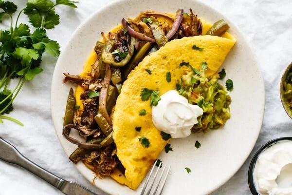 Omelette stuffed with carnitas and fajita veggies on a plate.