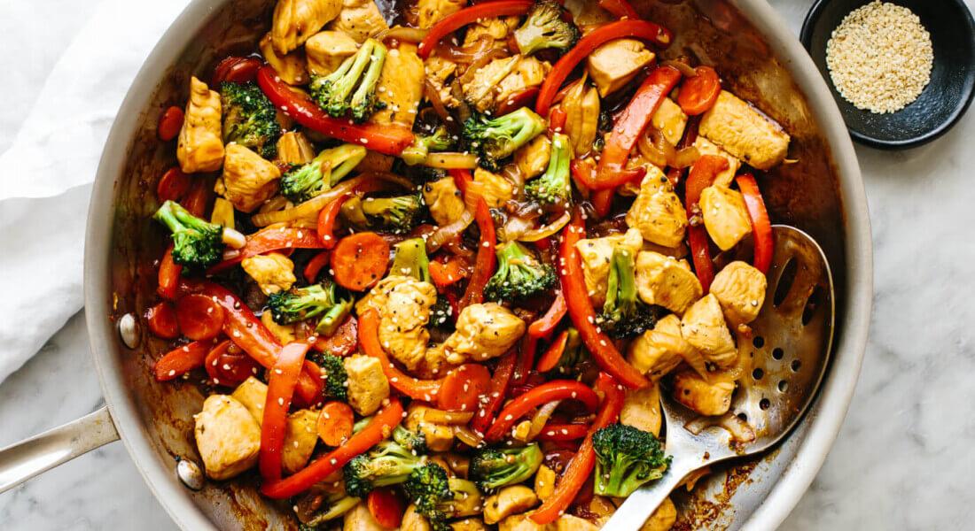 Chicken stir-fry in a pan next to sesame seeds.