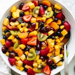 A large fruit salad bowl next to a napkin.