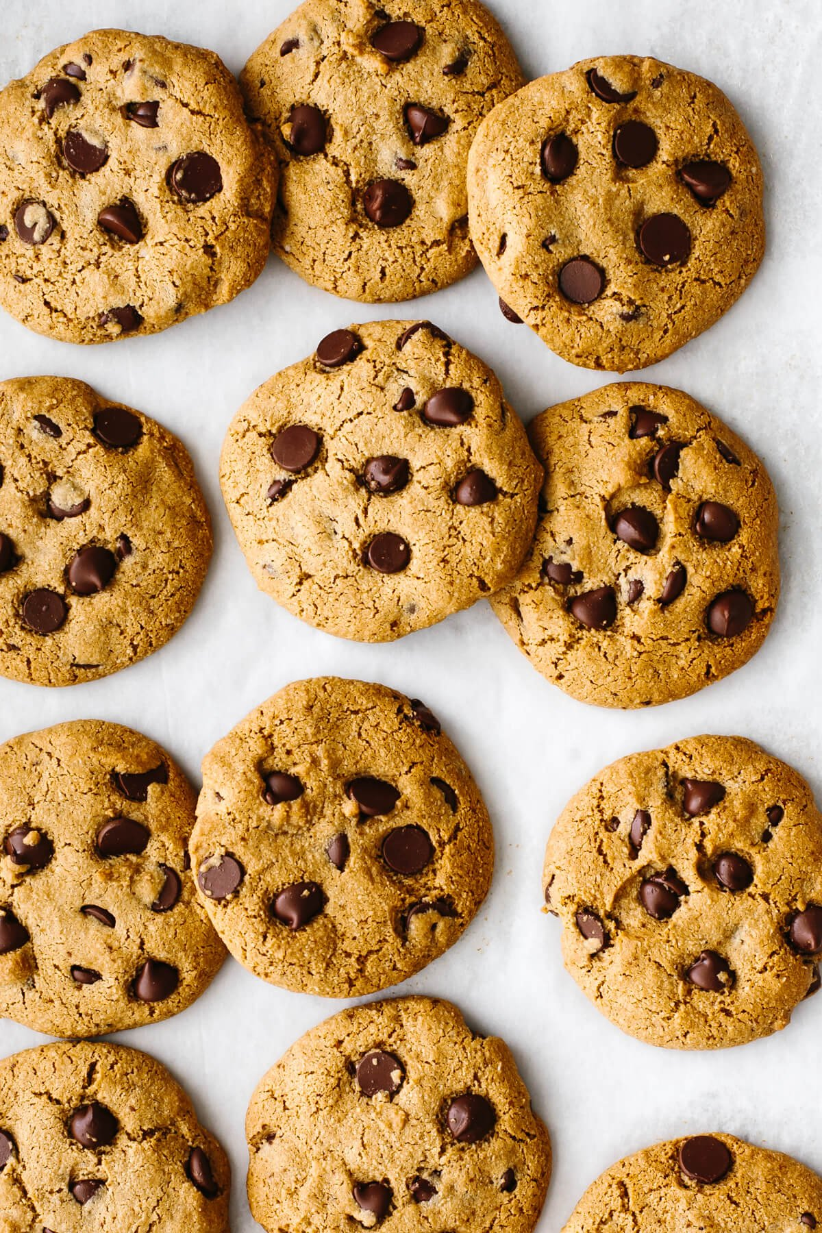 Gluten-free chocolate chip cookies spread out on a baking sheet.