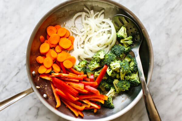 Sauteeing vegetables in a pan for chicken stir-fry.