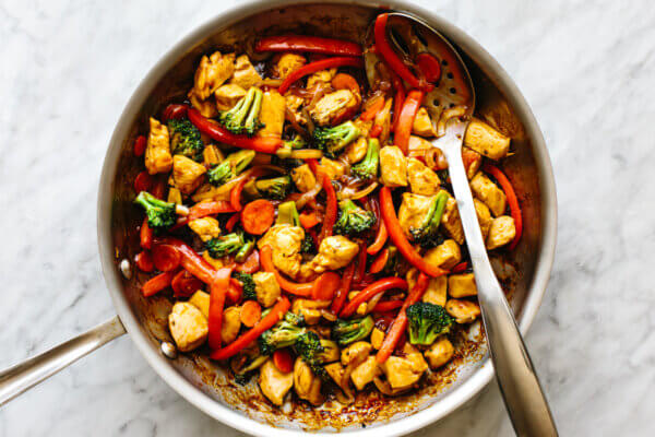 A pan with chicken stir-fry and a slotted spoon.