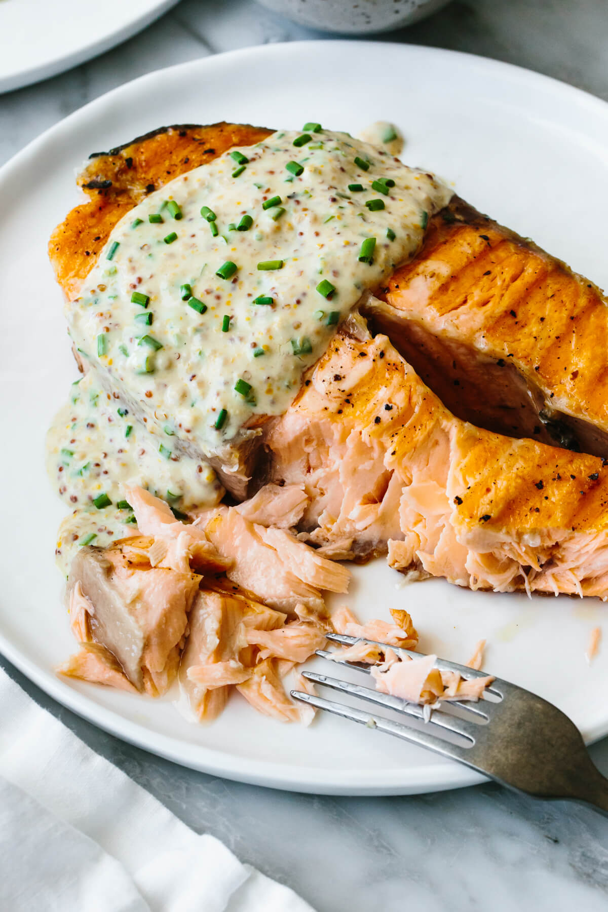 Grilled salmon steak on a plate with a fork
