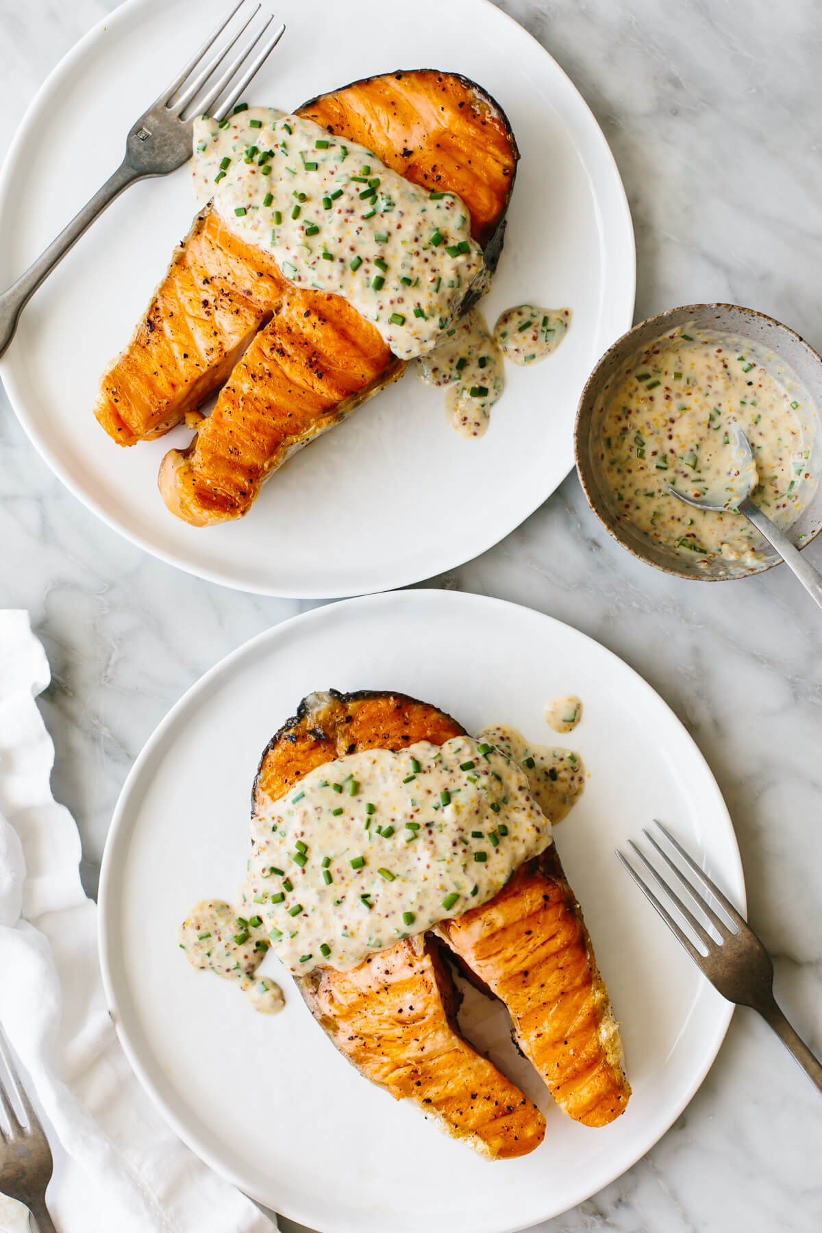 Grilled salmon steaks on two white plates
