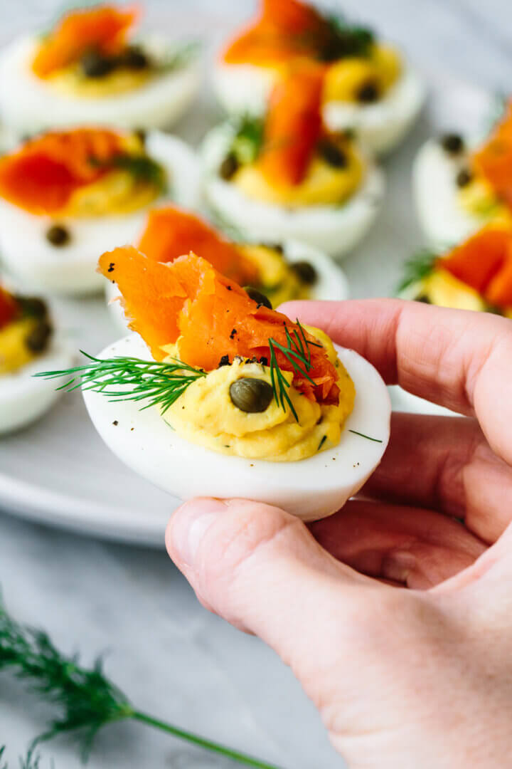Holding a single smoked salmon deviled egg in hand.