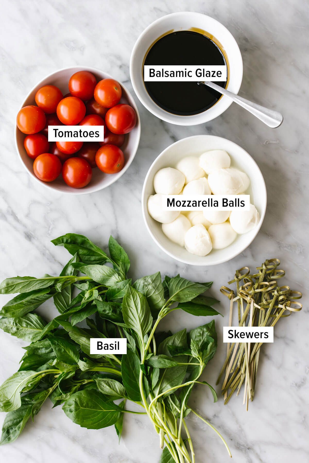 Ingredients for caprese skewers on a table.