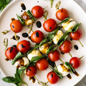 Caprese skewers with basil leaves on a plate