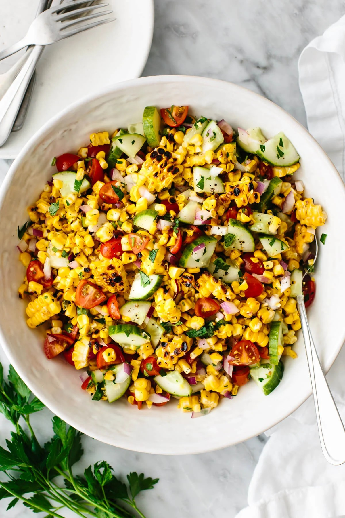 Grilled corn salad in a large white bowl.