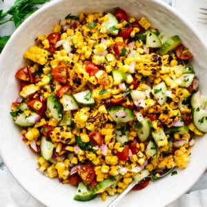 A large white bowl of corn salad next to parsley and a napkin