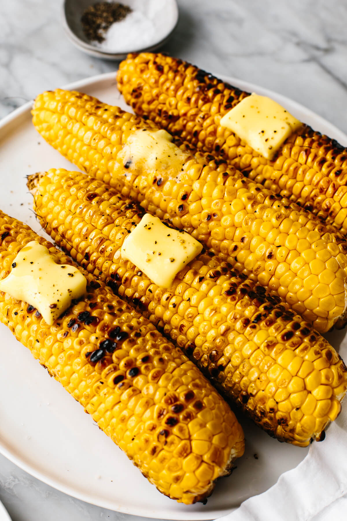 Grilled corn on the cobs withe butter on a plate