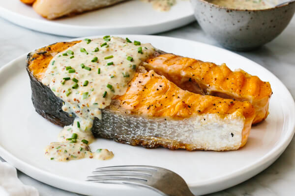 Salmon steak on a plate drizzled with yogurt sauce.