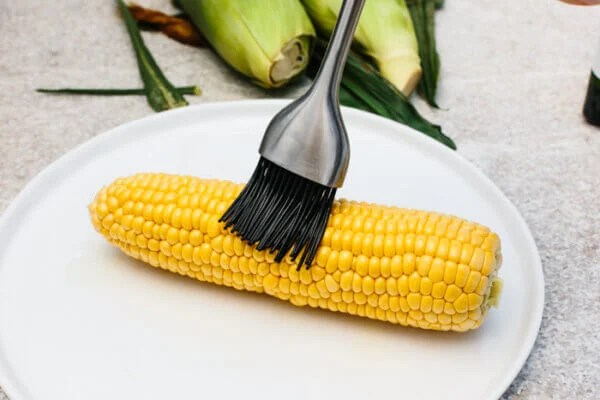 Brushing oil on a corn on the cob for grilling