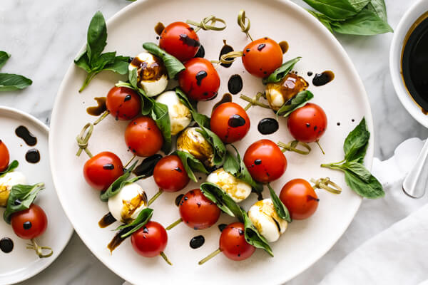 A plate with caprese skewers drizzled with balsamic glaze