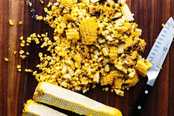 Shaving kernels off a corn on the cob for corn salad