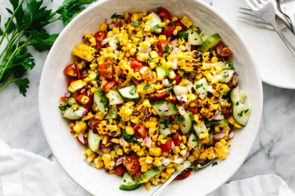 A white bowl of corn salad next to a fork.