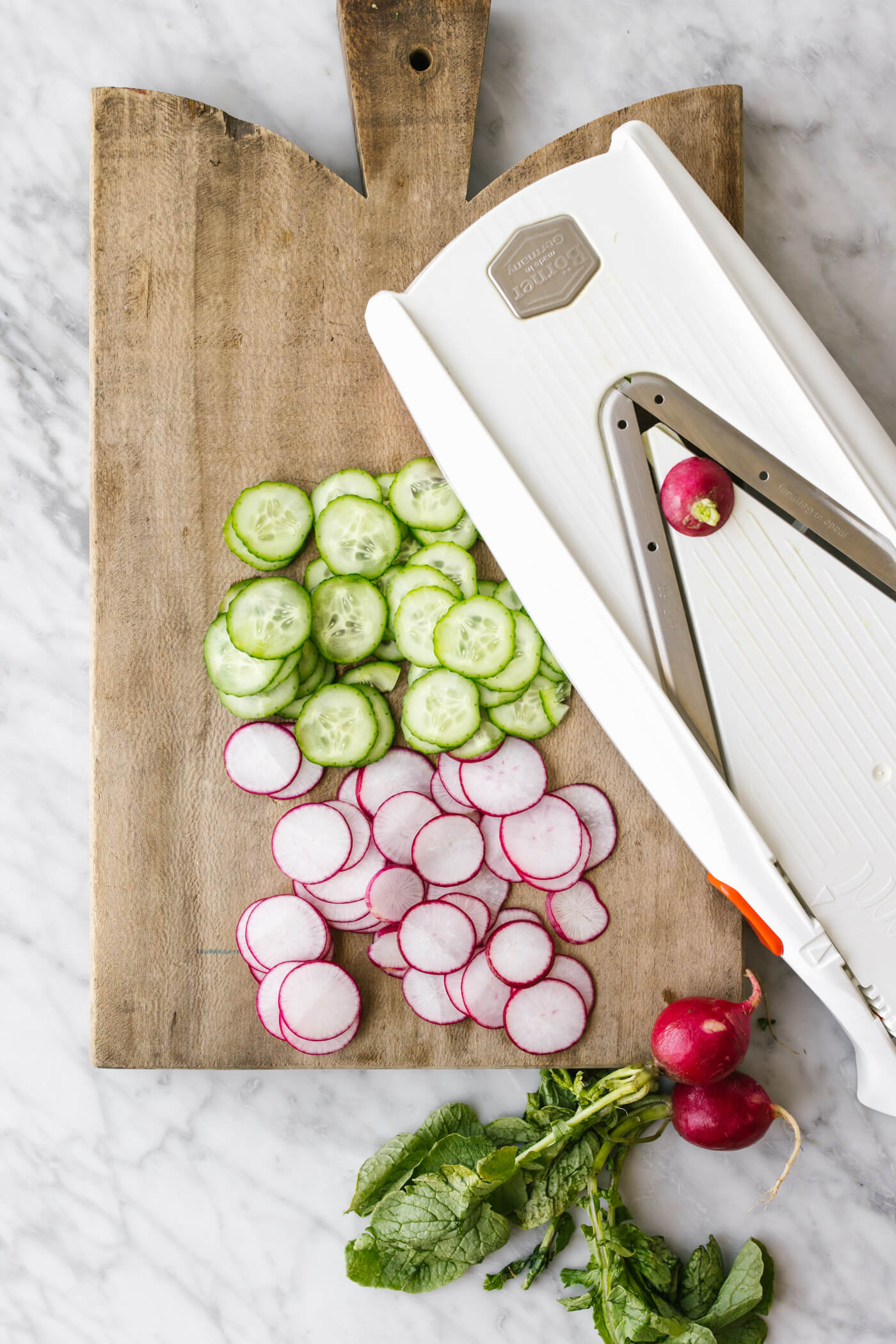 Slicing cucumbers and radish with a mandolin for a salad.
