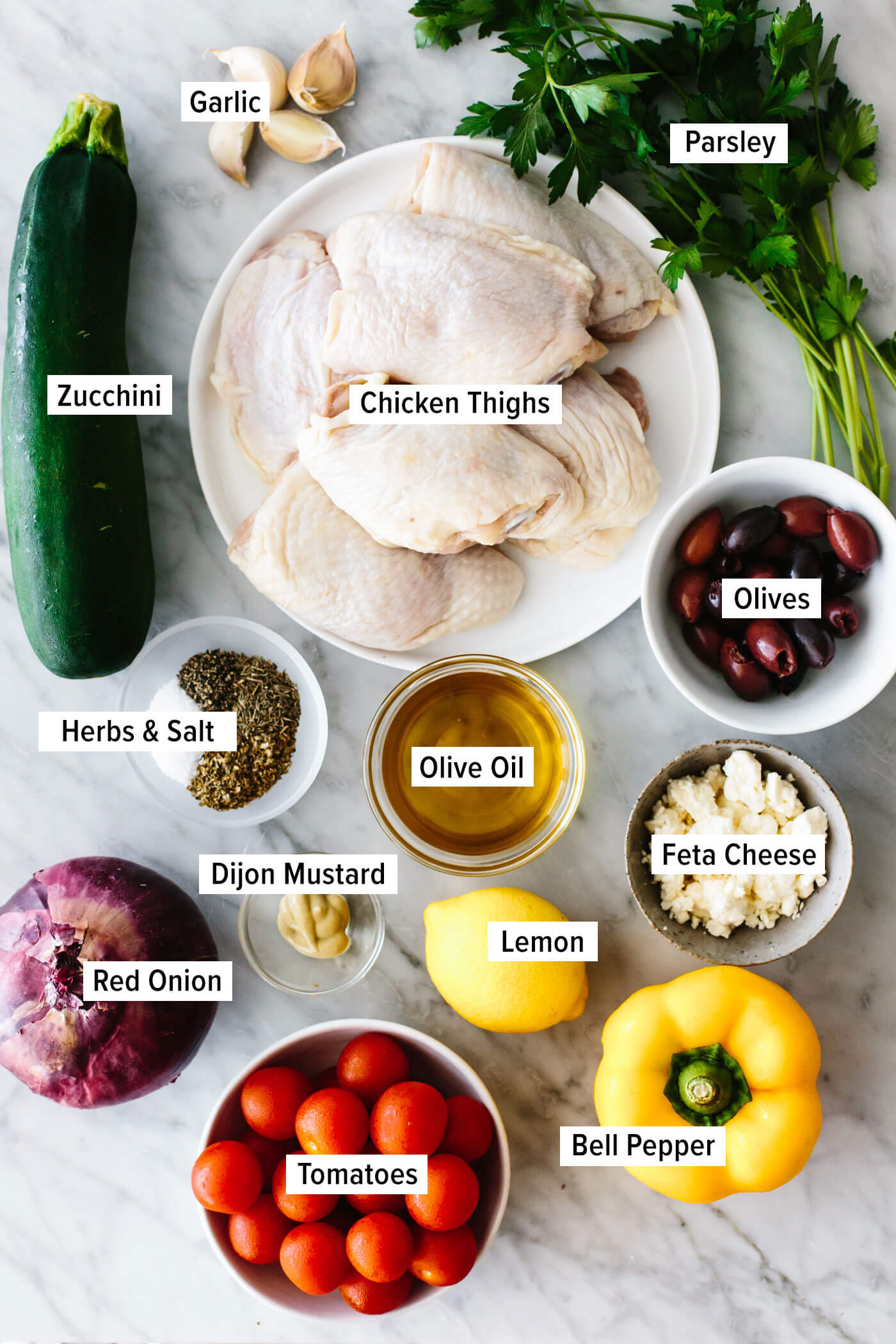 Ingredients for greek sheet pan chicken on a table.