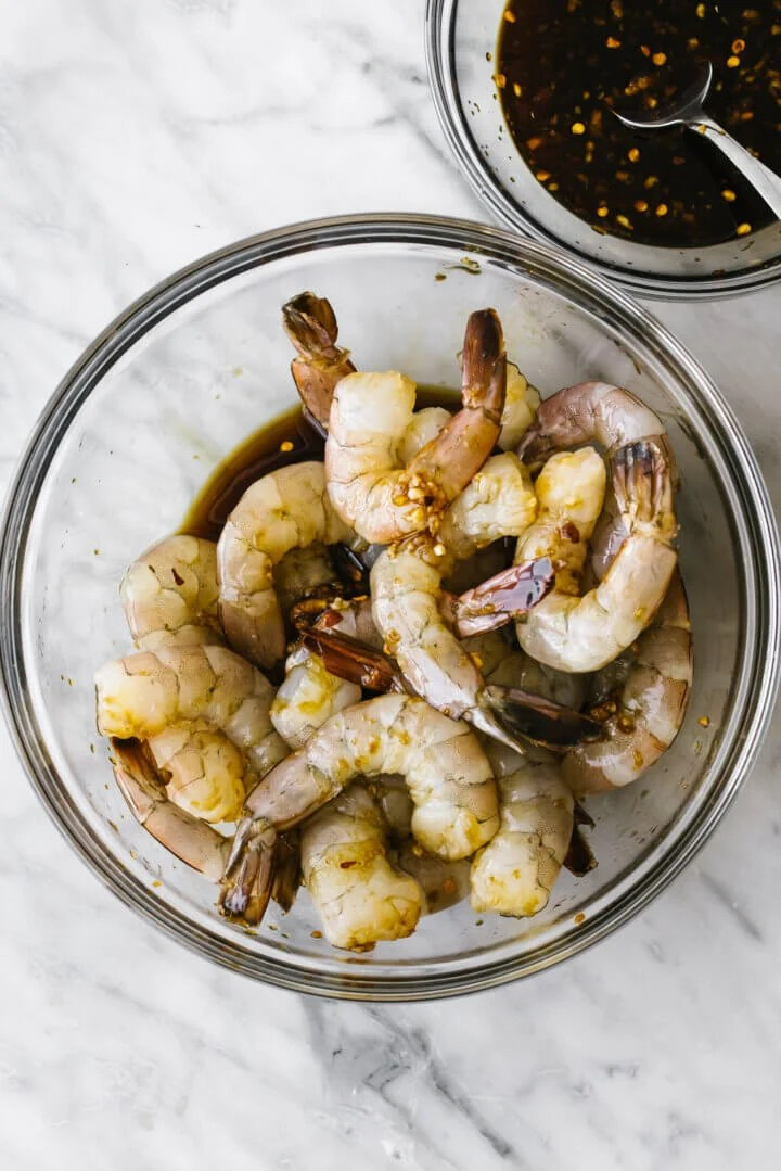 Marinating honey garlic shrimp in a glass bowl.