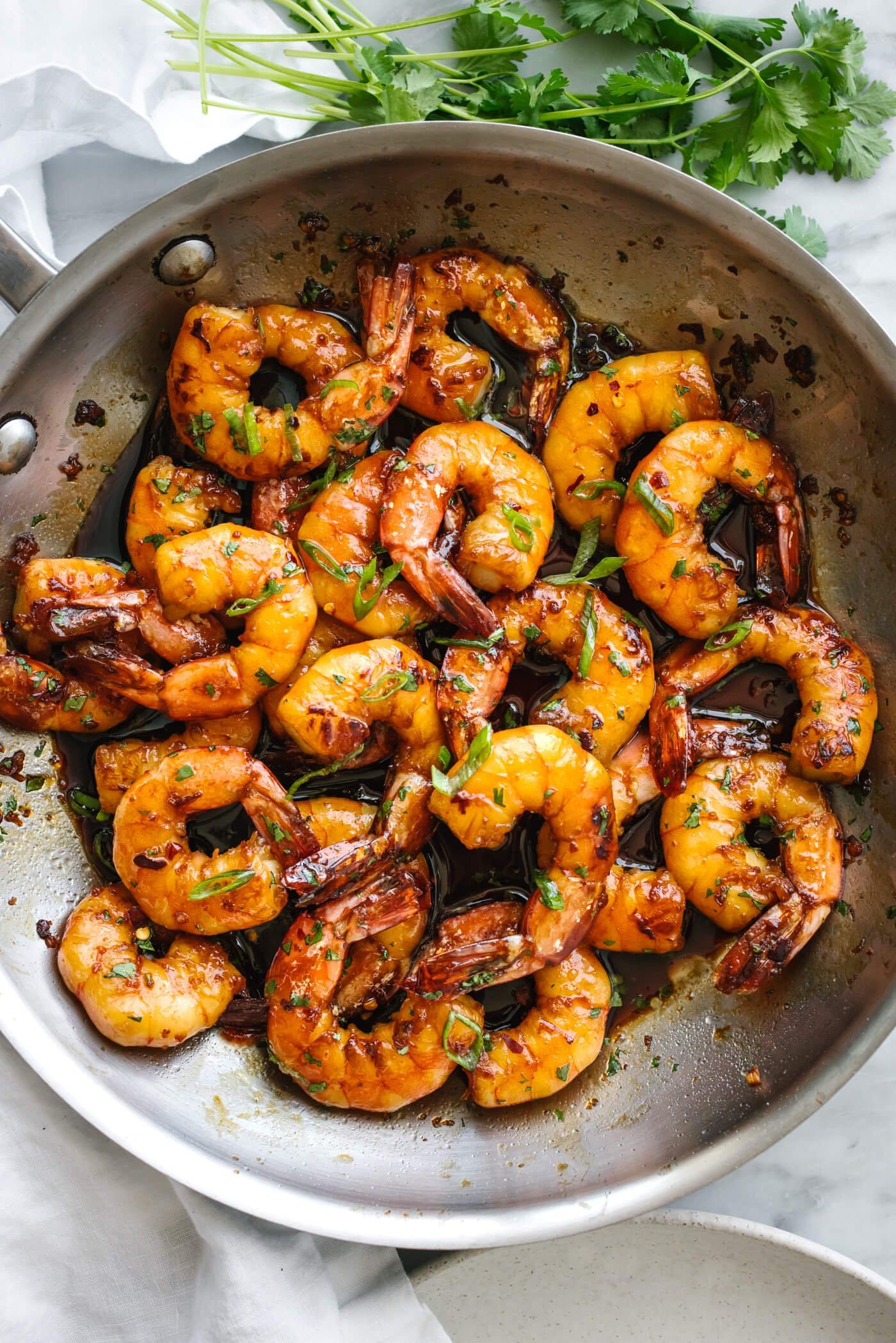 Honey garlic shrimp in a metal pan next to cilantro