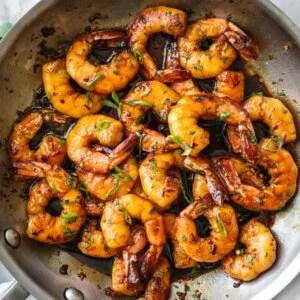 Honey garlic shrimp sauteed in a pan next to a napkin