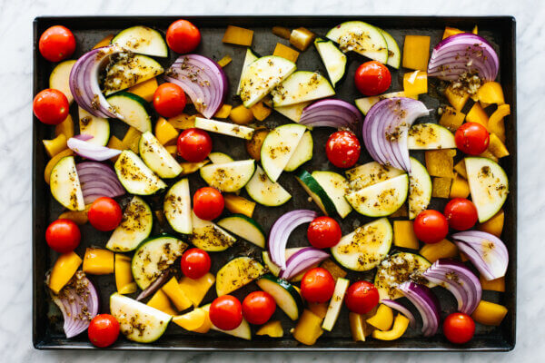 A sheet pan with roasted vegetables before adding Greek chicken.
