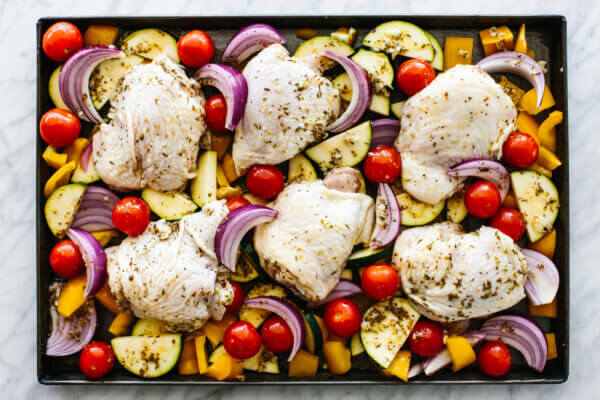 Greek chicken thighs with vegetables on a sheet pan.