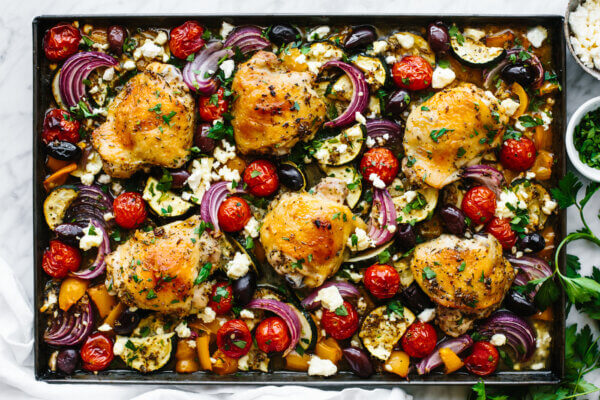 A large sheet pan with Greek chicken and roasted vegetables