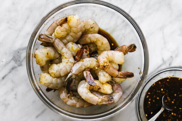 Marinating honey garlic shrimp in a large glass bowl