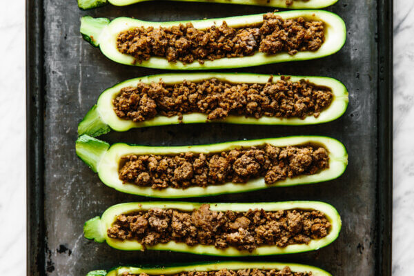 Filling zucchini boats with ground beef.