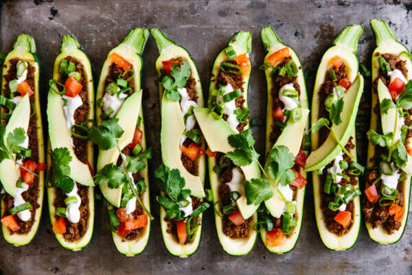 Taco stuffed zucchini boats lined up on a baking sheet