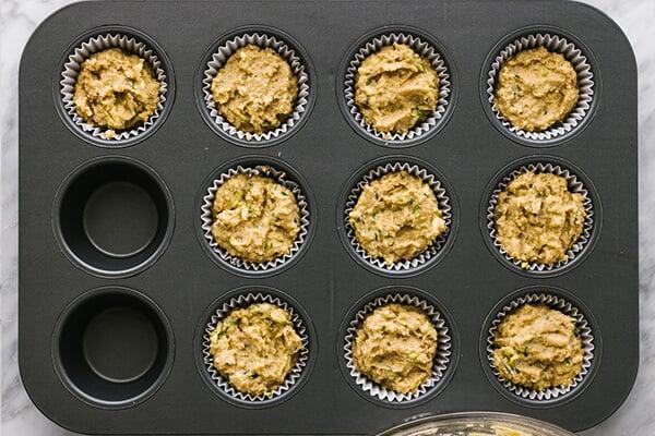 Adding healthy zucchini muffin batter into a muffin tin.