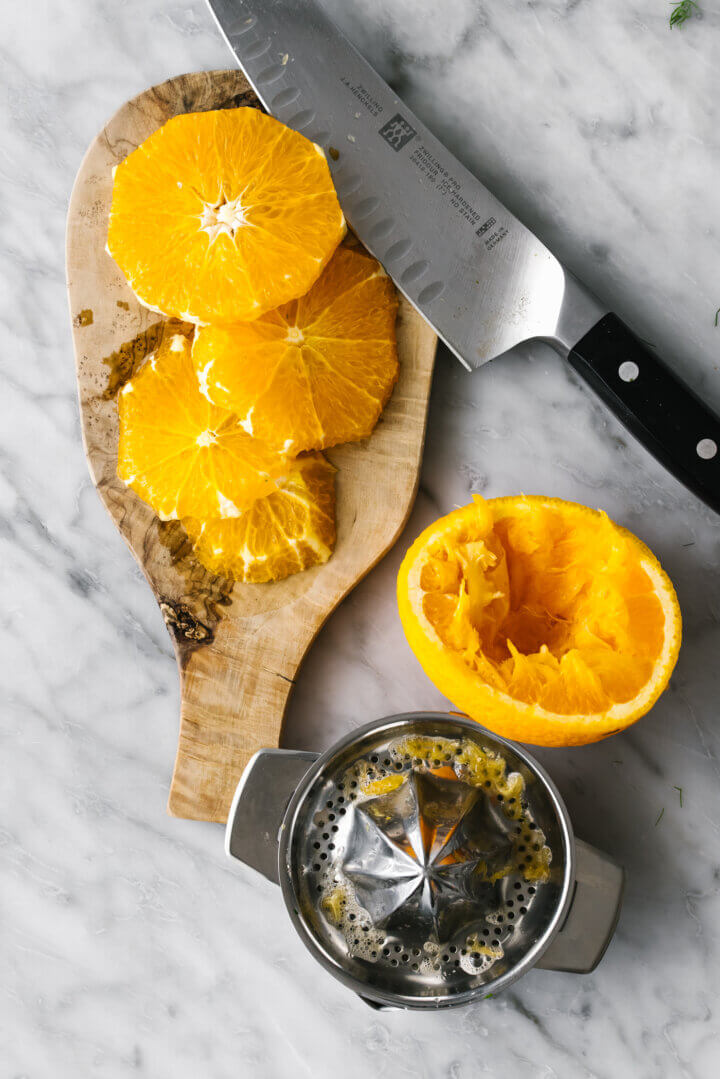 Sliced oranges with a knife for slow roasted salmon.