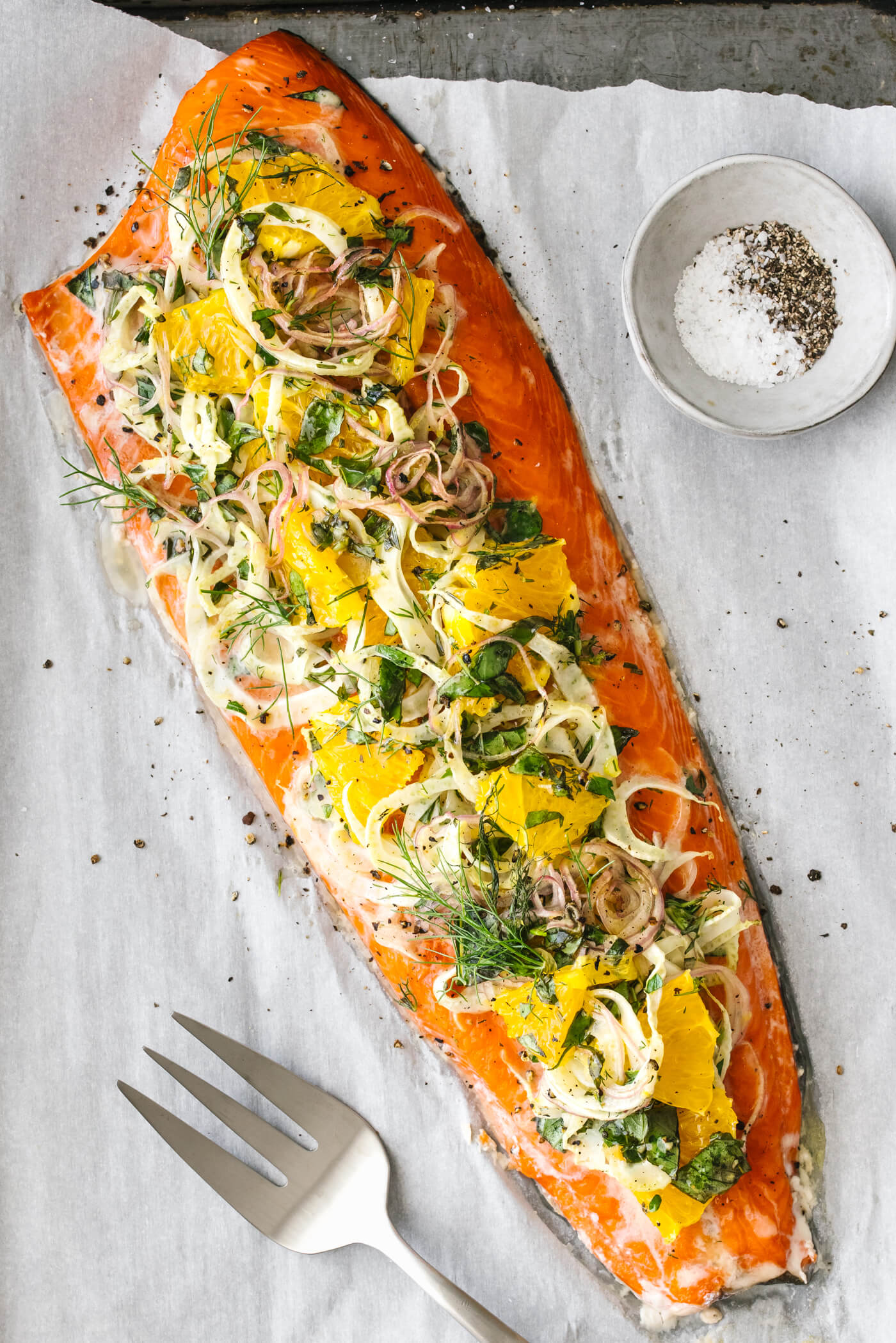Slow roasted salmon with orange, fennel, and herbs on a sheet pan.