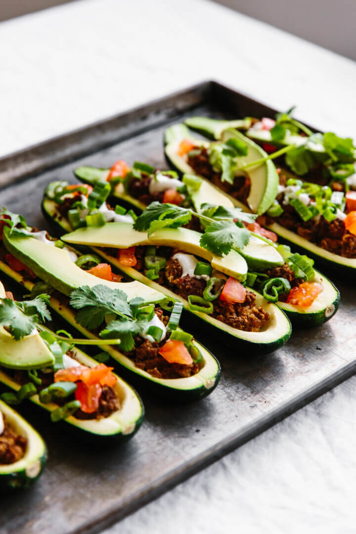 Stuffed zucchini boats with ground beef and taco toppings.